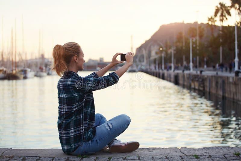 Mujer que presenta mientras que se fotografía en el teléfono móvil para la charla con los amigos en fin de semana del verano, imágenes de archivo libres de regalías