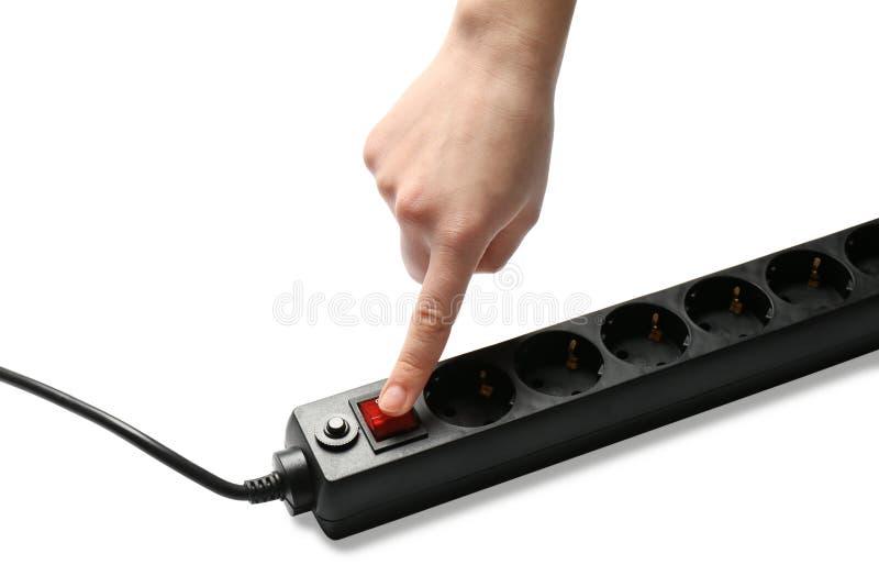 Mujer que presiona el botón de encendido del cable de extensión en blanco, primer El equipo del electricista fotografía de archivo