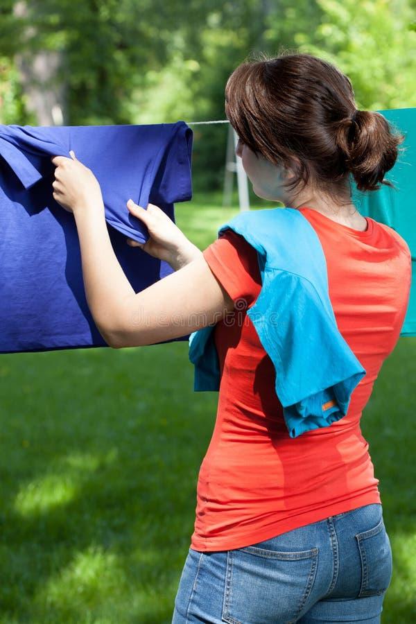Mujer que quita el lavadero de cuerda para tender la ropa foto de archivo