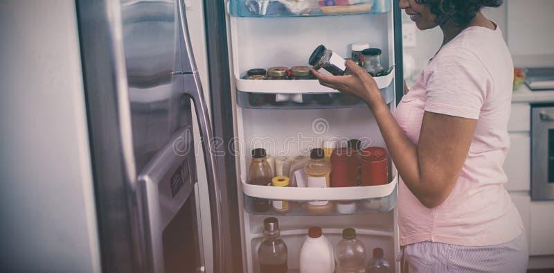 Mujer que quita la botella del refrigerador en cocina imágenes de archivo libres de regalías