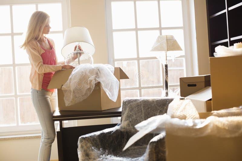 Mujer que quita la lámpara de la caja móvil en la nueva casa imagenes de archivo