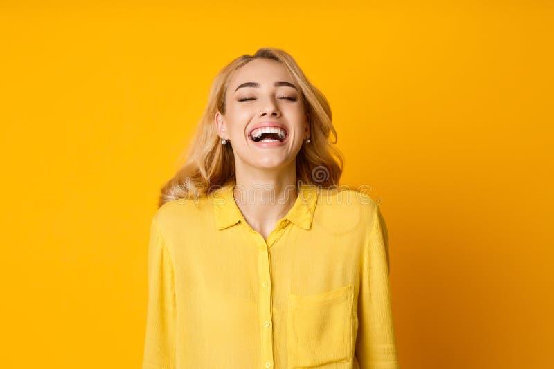 Mujer que ríe hacia fuera ruidosamente, broma divertida de la audición fotos de archivo libres de regalías