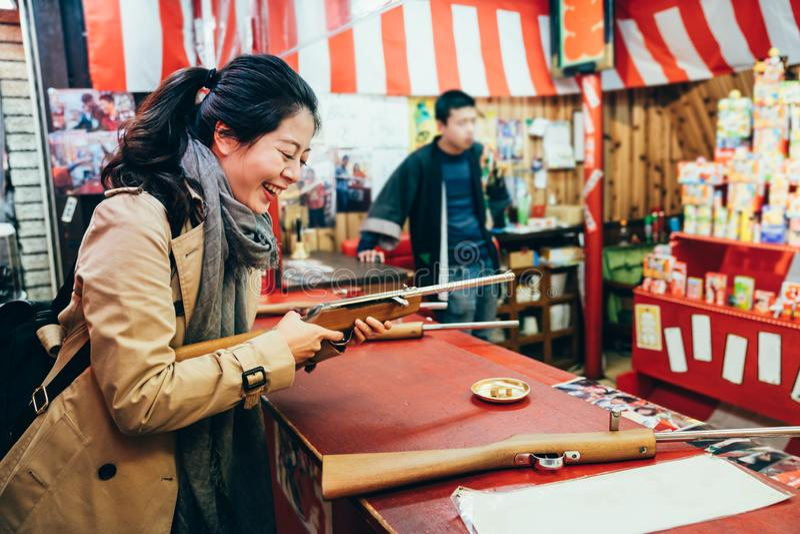 Mujer que ríe jugando al juego que tira en festival imagen de archivo libre de regalías