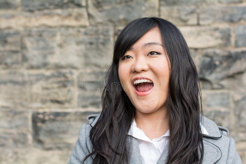 Mujer que ríe por una pared de piedra imagen de archivo