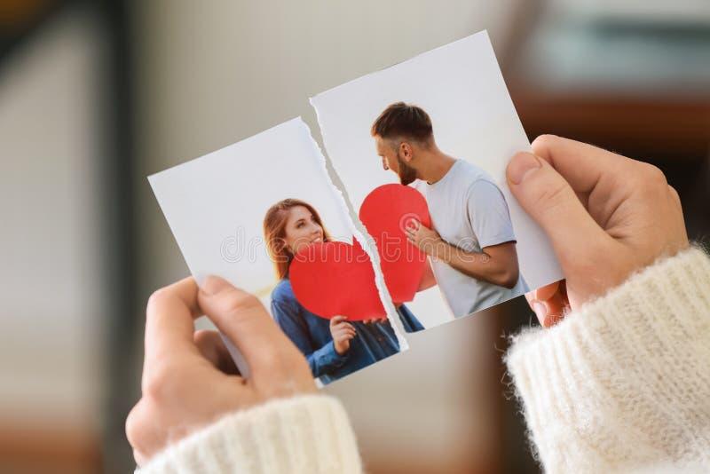 Mujer que rasga para arriba la foto de los pares felices, primer Concepto de divorcio fotos de archivo
