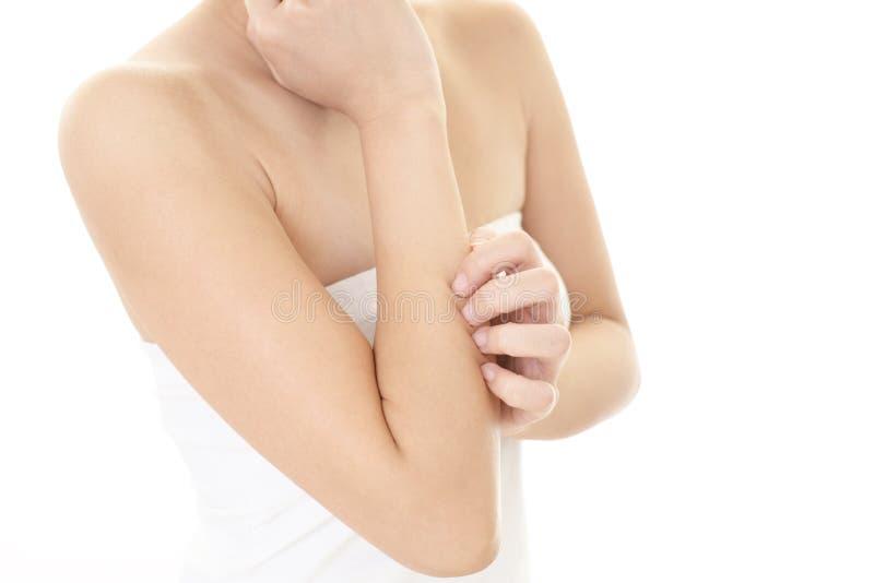 Mujer que rasguña su brazo que pica fotografía de archivo