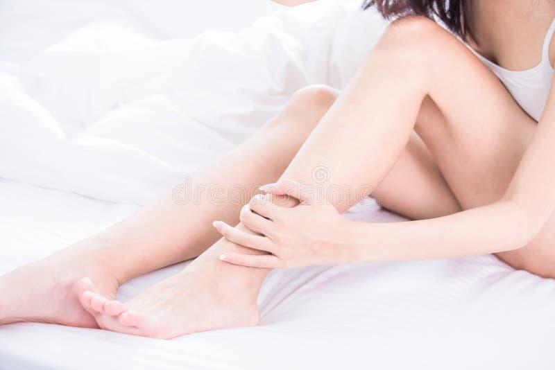 Mujer que rasguña su pierna foto de archivo libre de regalías