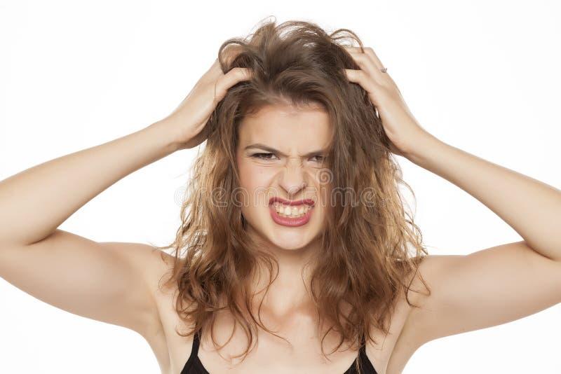 Mujer que rasguña su cabeza fotografía de archivo