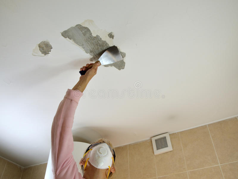 Mujer que raspa un techo foto de archivo