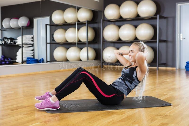 Mujer que realiza crujidos en el ejercicio Mat In Gym imagenes de archivo