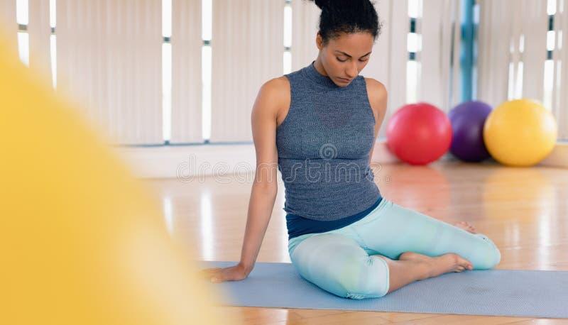 Mujer que realiza yoga en gimnasio fotos de archivo