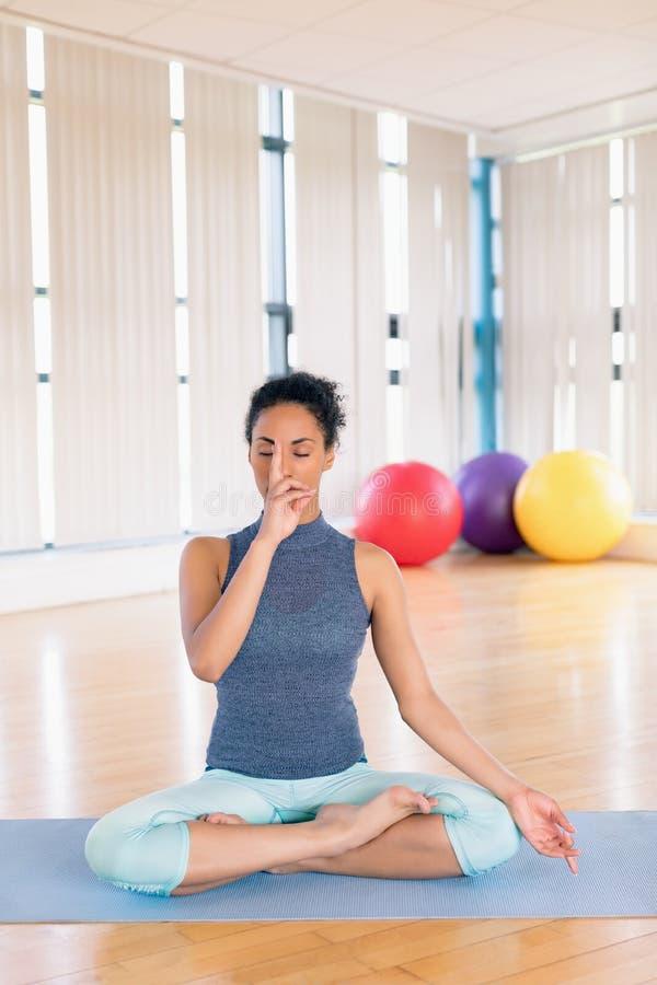 Mujer que realiza yoga en gimnasio imagen de archivo libre de regalías