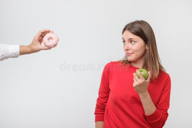 Mujer que rechaza el buñuelo o el postre y que elige la comida sana fotos de archivo libres de regalías