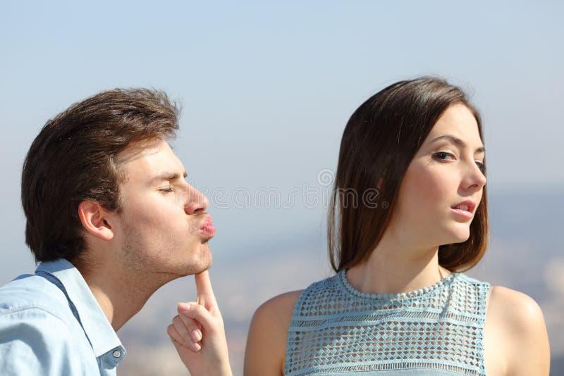 Mujer que rechaza un beso del amigo fotos de archivo libres de regalías