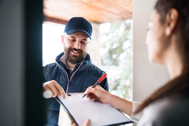 Mujer que recibe el paquete de hombre de entrega en la puerta imagen de archivo libre de regalías