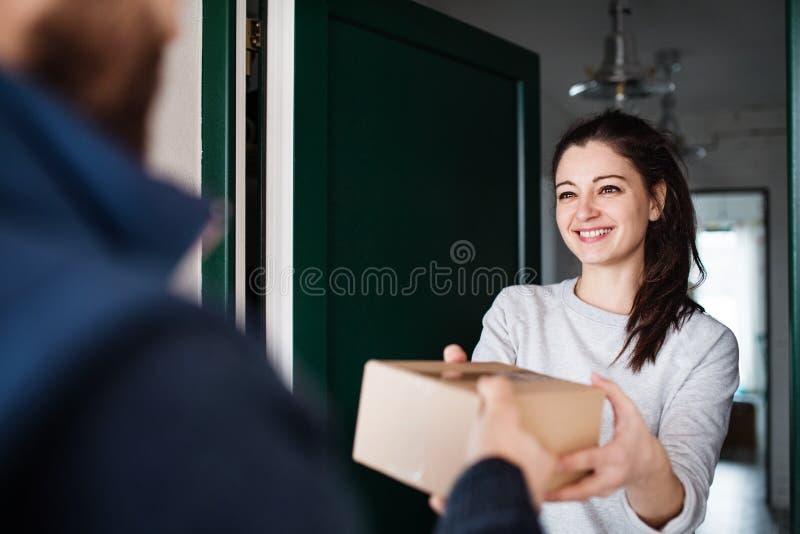 Mujer que recibe el paquete de hombre de entrega en la puerta fotos de archivo libres de regalías
