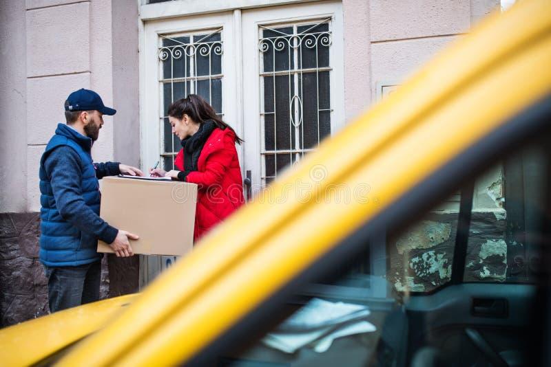 Mujer que recibe el paquete de hombre de entrega en la puerta fotografía de archivo
