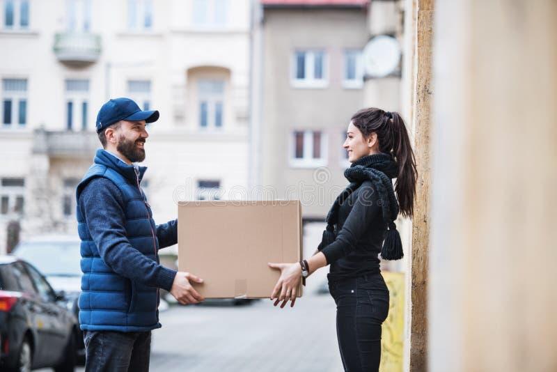 Mujer que recibe el paquete de hombre de entrega en la puerta fotografía de archivo libre de regalías
