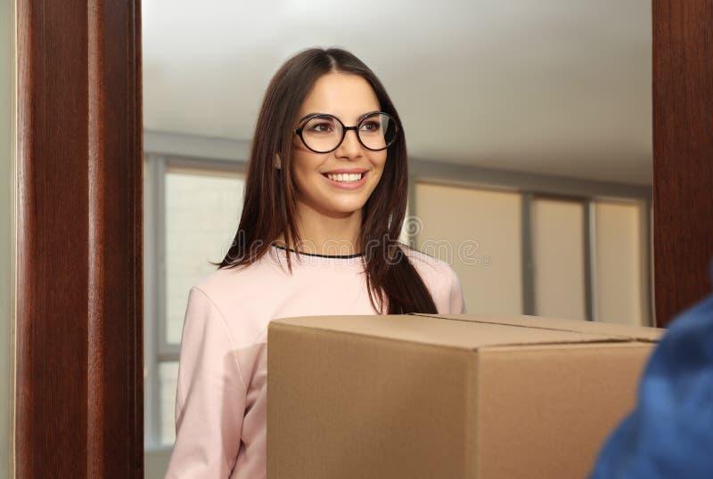 Mujer que recibe el paquete de mensajero del servicio de entrega imagenes de archivo