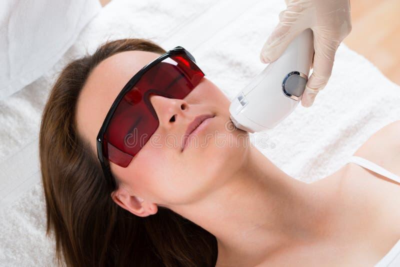 Mujer que recibe el tratamiento del laser Epilation imagen de archivo