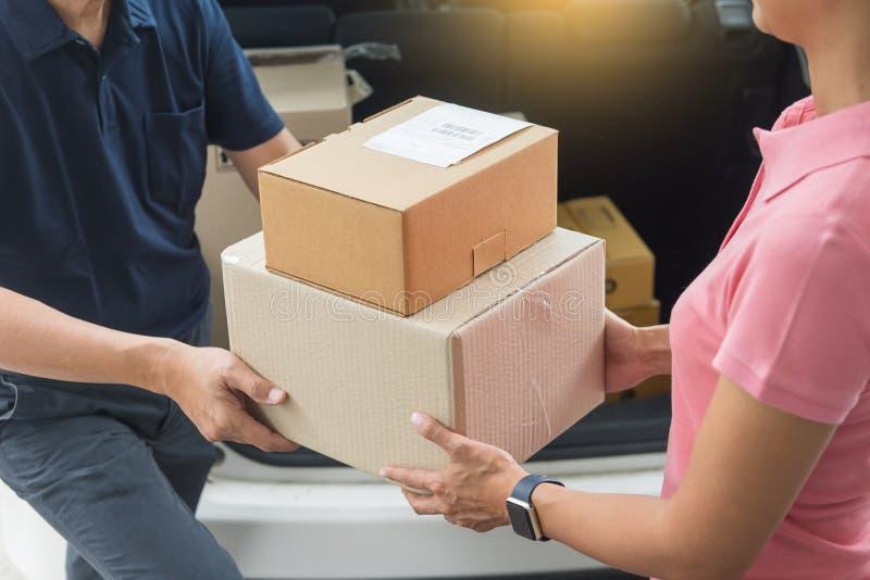 Mujer que recibe la caja de cartón del paquete de llevar del hombre de entrega foto de archivo