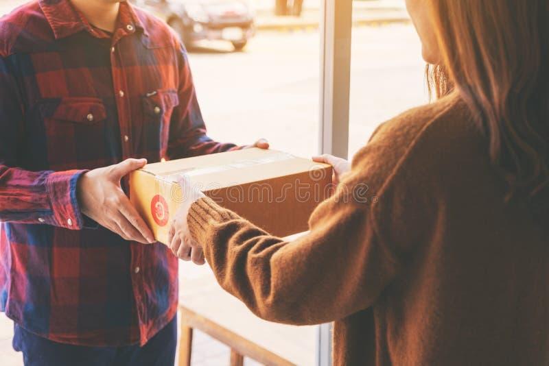 Mujer que recibe la caja del paquete de hombre de entrega imagen de archivo libre de regalías