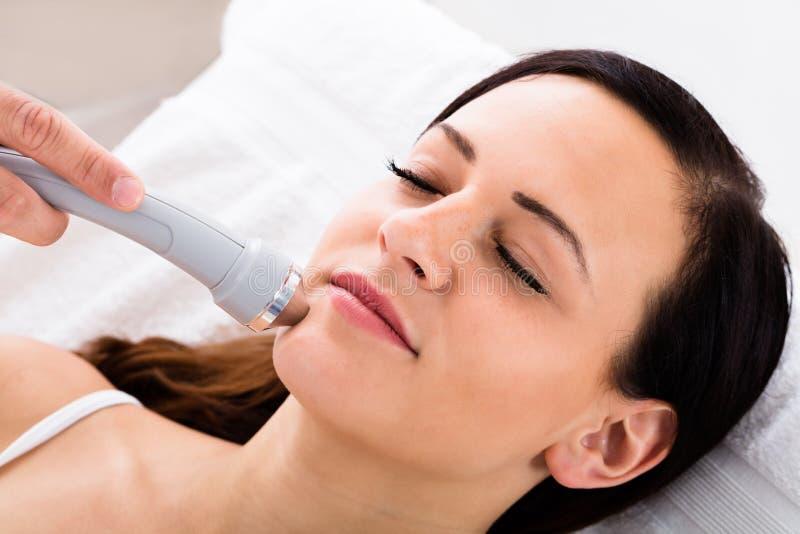 Mujer que recibe masaje de cara de terapeuta imagen de archivo