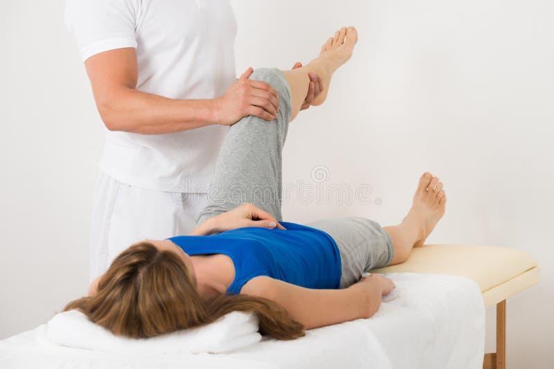 Mujer que recibe masaje de la pierna en balneario fotografía de archivo