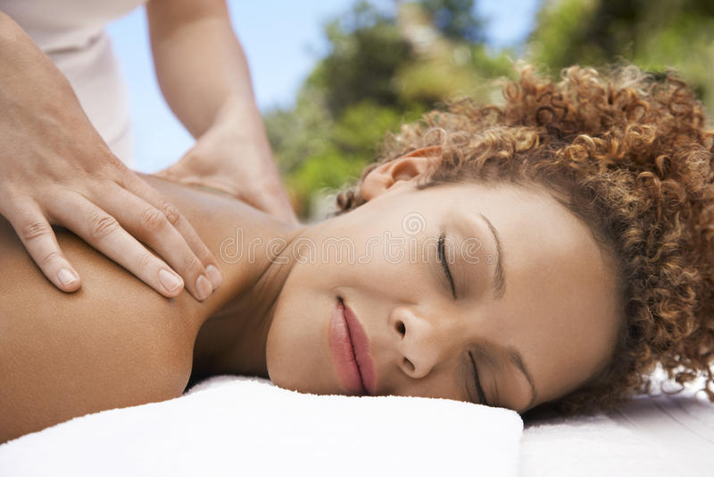Mujer que recibe masaje del hombro de masajista fotografía de archivo