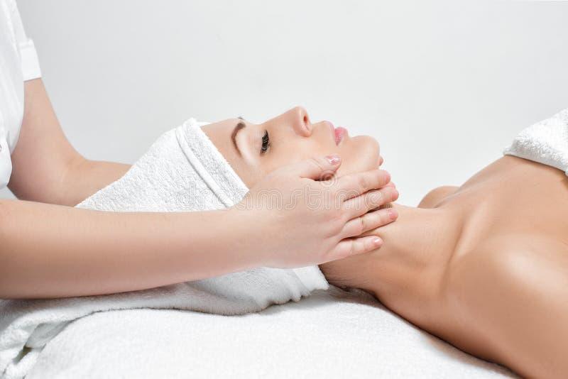 Mujer que recibe masaje facial en el salón del balneario imágenes de archivo libres de regalías