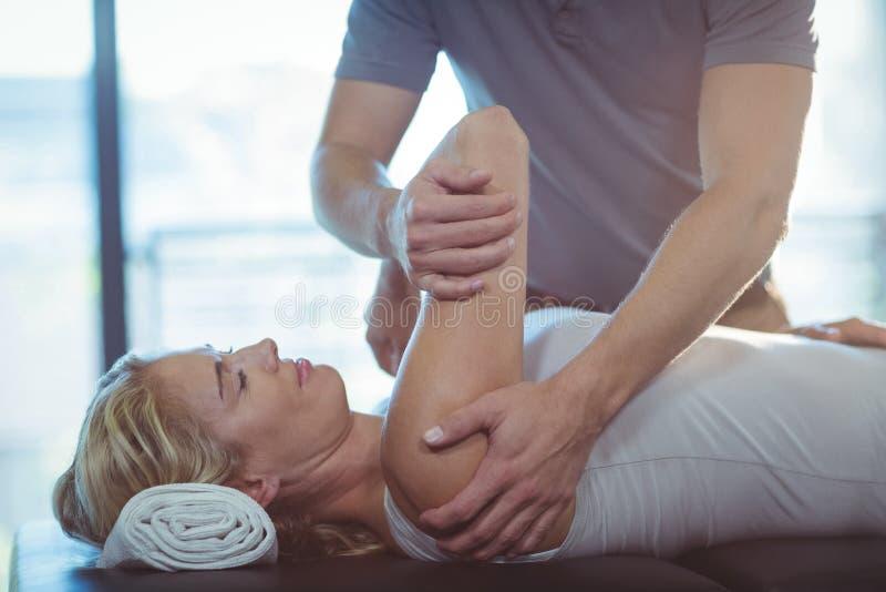 Mujer que recibe terapia del hombro de fisioterapeuta imágenes de archivo libres de regalías