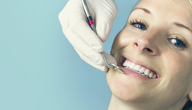 Mujer que recibe un control dental para arriba de su dentista fotografía de archivo libre de regalías
