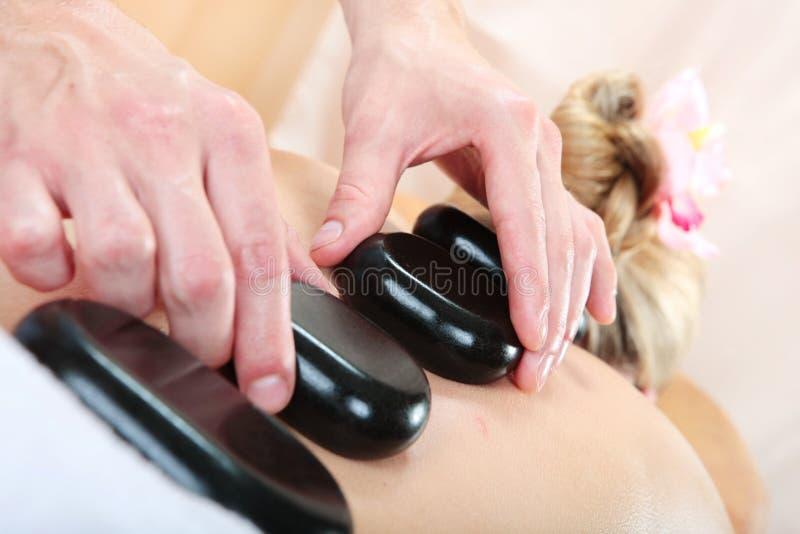 Mujer que recibe un masaje con la piedra caliente en un balneario imágenes de archivo libres de regalías
