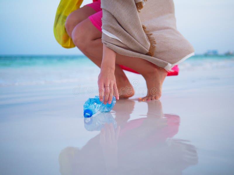 Mujer que recoge basura plástica en la playa imagen de archivo