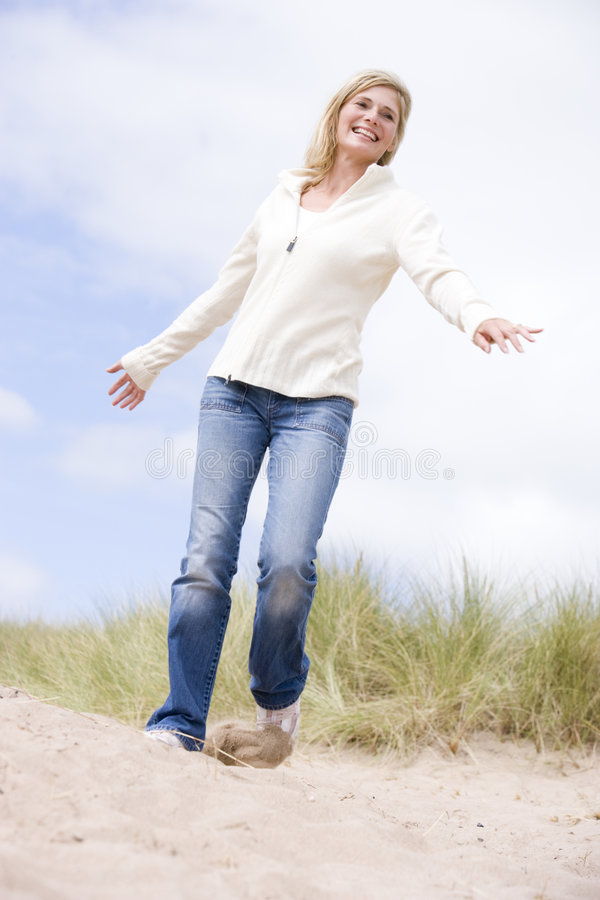 Mujer que recorre en la sonrisa de la playa imágenes de archivo libres de regalías