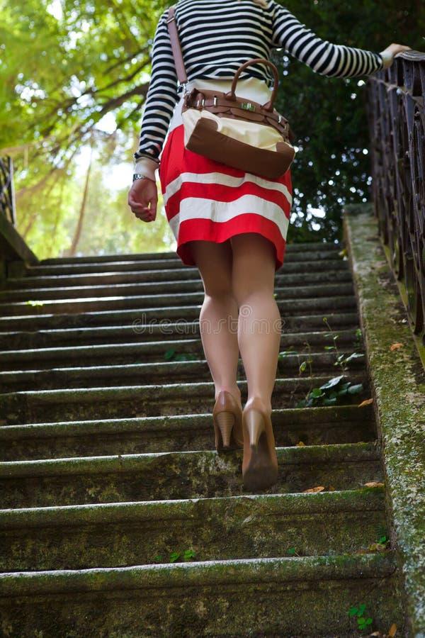 Mujer que recorre encima de las escaleras foto de archivo
