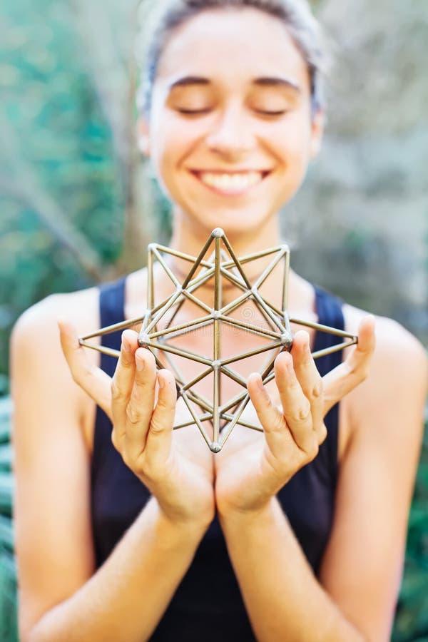 Mujer que reflexiona sobre geometría sagrada foto de archivo