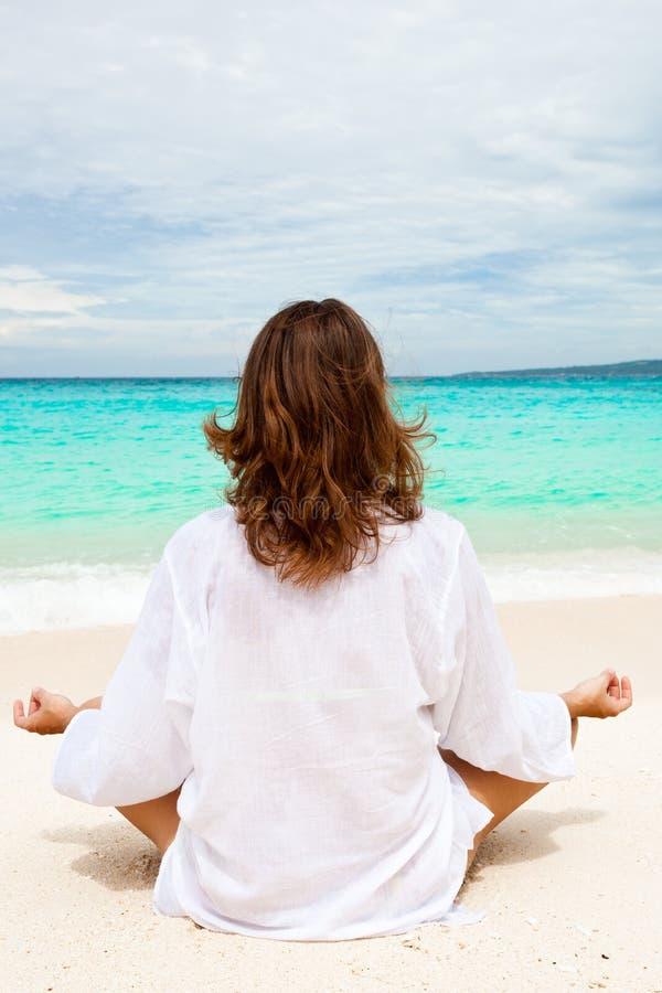 Mujer que reflexiona sobre la playa fotos de archivo
