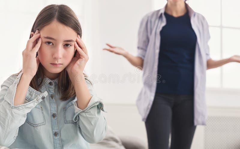 Mujer que regaña a su hija adolescente en casa fotografía de archivo