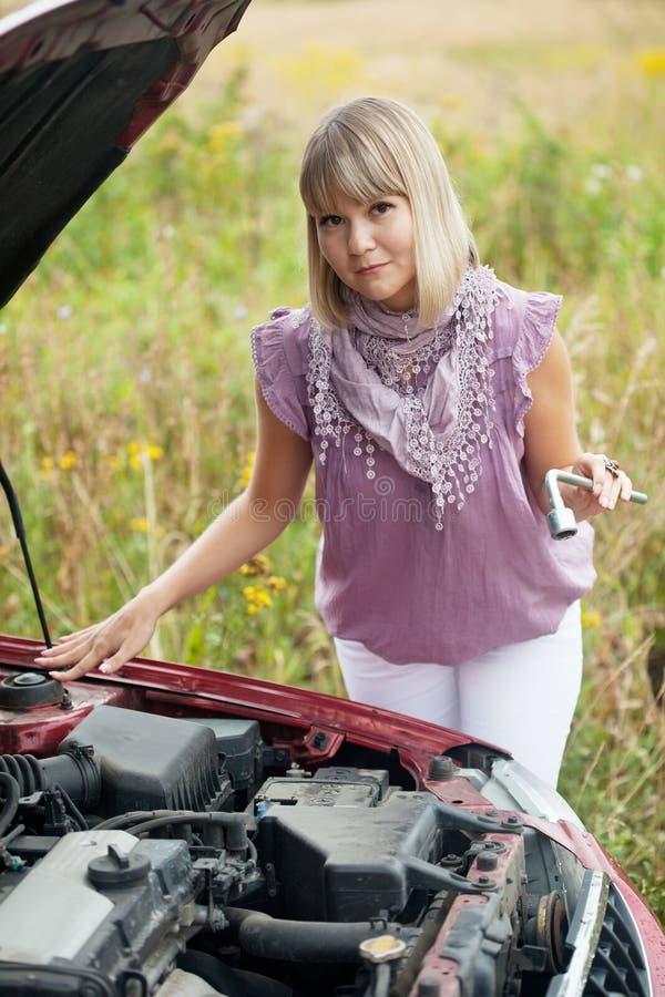 Mujer que repara su coche foto de archivo libre de regalías