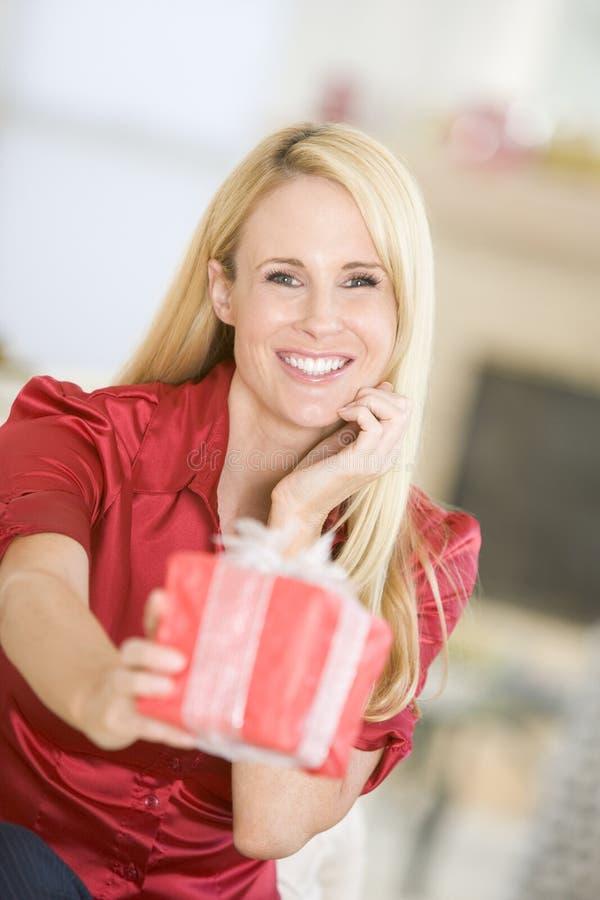 Mujer que reparte el regalo de Navidad foto de archivo libre de regalías