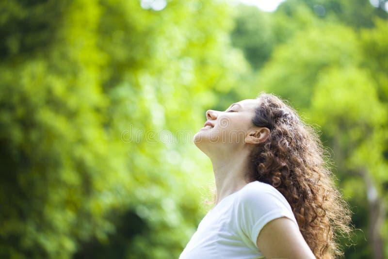 Mujer que respira el aire fresco al aire libre en verano imagenes de archivo