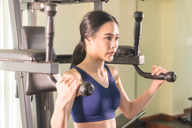 Mujer que resuelve el ABS en la máquina de la aptitud del gimnasio imagenes de archivo