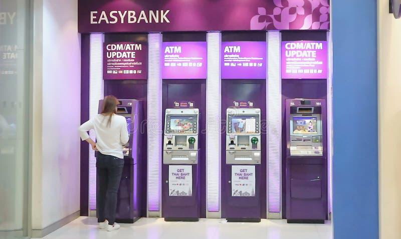 Mujer que retira el dinero de la tarjeta de crédito en el cajero automático en centro comercial del adaptador 21 en el camino Ban fotografía de archivo libre de regalías