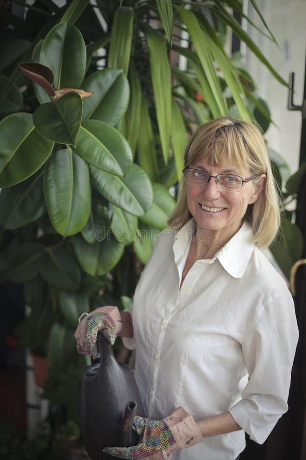 Mujer que riega las plantas foto de archivo