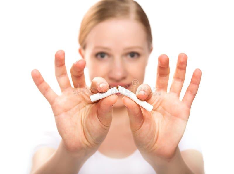 Mujer que rompe el cigarrillo. el fumar de la parada del concepto foto de archivo