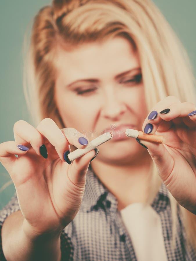 Mujer que rompe el cigarrillo, librándose del apego fotos de archivo