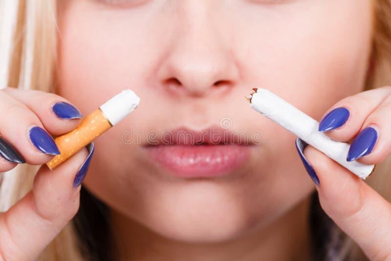Mujer que rompe el cigarrillo, librándose del apego imagen de archivo
