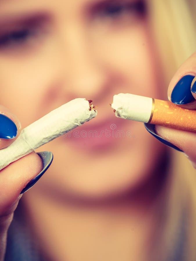 Mujer que rompe el cigarrillo, librándose del apego imagen de archivo libre de regalías