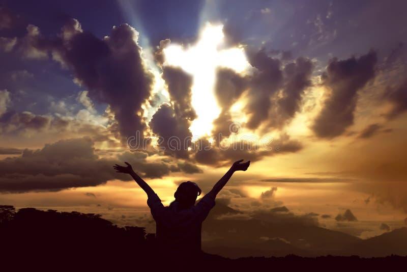 Mujer que ruega a dios con el rayo de la luz que forma la cruz en el cielo fotos de archivo